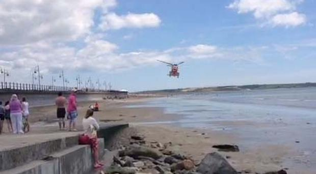 A man was airlifted to hospital after suffering suspected heart attack amid scorching beach heat