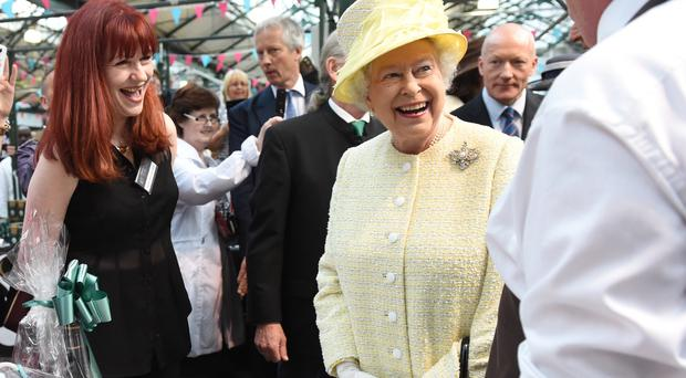 Her Majesty laughs with stallholders at St George's Market