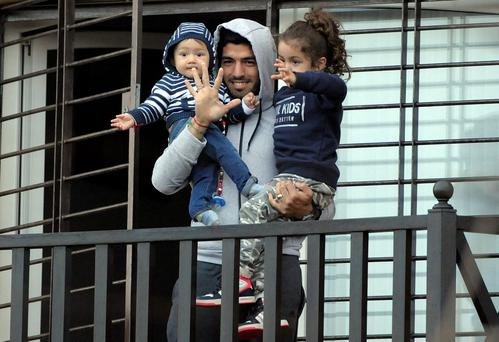 Uruguay's soccer player Luis Suarez holds his children as he greets fans from their home's balcony on the outskirts of Montevideo, Uruguay, Friday, June 27, 2014. (AP Photo)