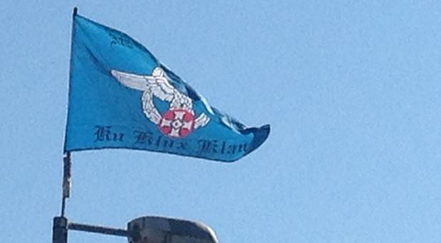 """The blue flag says """"New Order Knights"""" and underneath, """"Ku Klux Klan"""""""