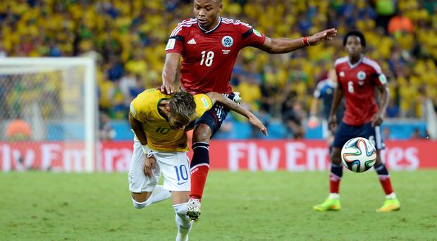 Neymar of Brazil is challenged by Juan Camilo Zuniga of Colombia during the 2014 FIFA World Cup Brazil Quarter Final match between Brazil and Colombia at Castelao on July 4, 2014 in Fortaleza, Brazil. This tackle resulted in injury to Neymar and ended the player's World Cup. (Photo by Jamie McDonald/Getty Images)