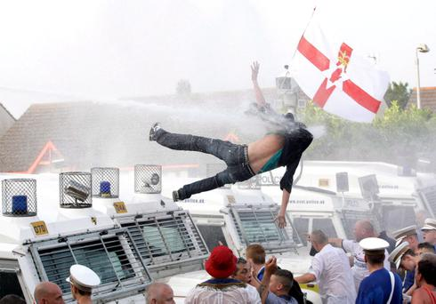 The photograph that went global: A rioter is thrown off a police Land Rover by water cannon after trouble flared in the Woodvale area in 2013. Pic David Fitzgerald