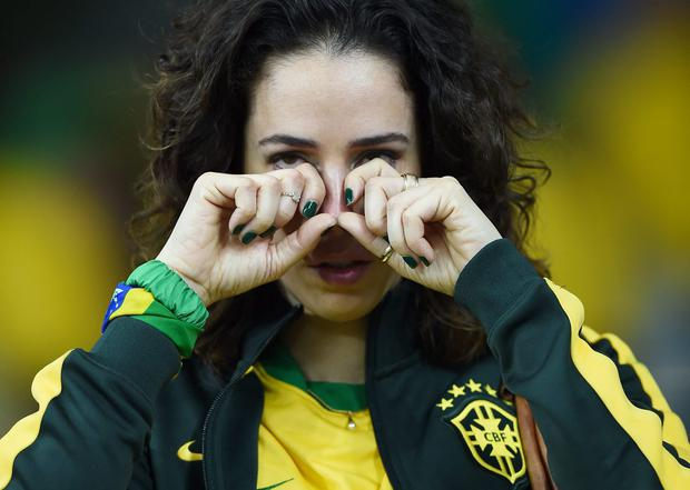 An emotional Brazil fan reacts after being defeated by Germany 7-1 during the 2014 FIFA World Cup Brazil Semi Final match between Brazil and Germany at Estadio Mineirao on July 8, 2014 in Belo Horizonte, Brazil. (Photo by Laurence Griffiths/Getty Images)