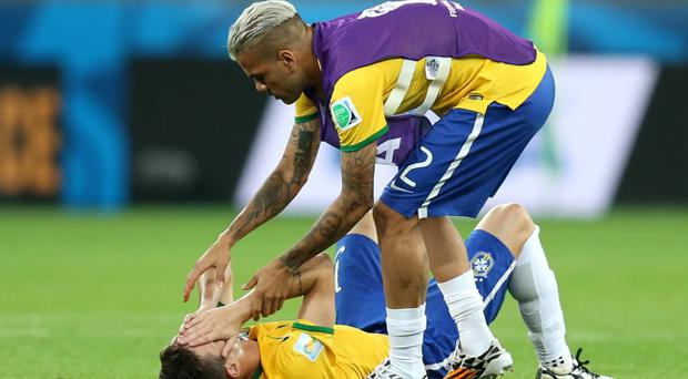 Brazil's Oscar (on floor) has to be consoled by teammate Dani Alves as he shows emotion after the final whistle during the FIFA World Cup Semi Final at Estadio Mineirao, Belo Horizonte, Brazil. PRESS ASSOCIATION Photo. Picture date: Tuesday July 8, 2014. See PA story SOCCER Germany. Photo credit should read: Mike Egerton/PA Wire. RESTRICTIONS: Editorial use only. No commercial use. No use with any unofficial 3rd party logos. No manipulation of images. No video emulation