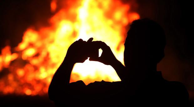Members of the public take photographs at a bonfire