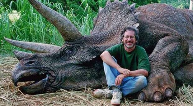 The photograph shows Stephen Spielberg sitting in front of a 'dead' triceratops
