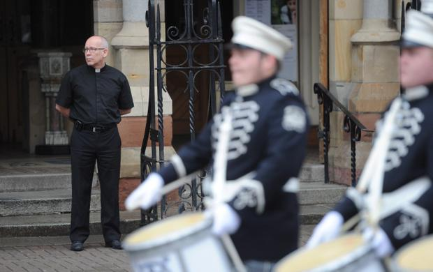 Fr Michael Sheehan watches a loyalist band parade past St Patrick's Church on Donegal Street, Belfast. Photo: Colm Lenaghan/Pacemaker