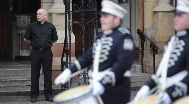 Fr Michael Sheehan watches a loyalist band parade past St Patrick's Church on Donegall Street on Saturday morning