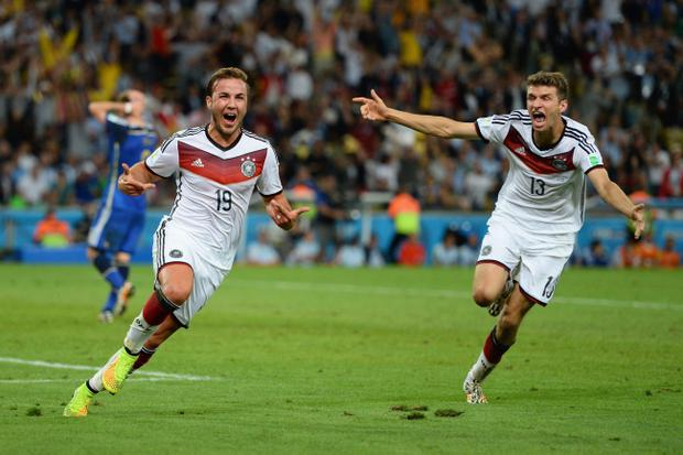 Mario Goetze of Germany (L) celebrates scoring his team's goal with Thomas Mueller against Argentina