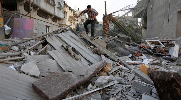 A Palestinian walks on the rubble from a damaged house following an overnight Israeli missile strike in Gaza City, Tuesday, July 15