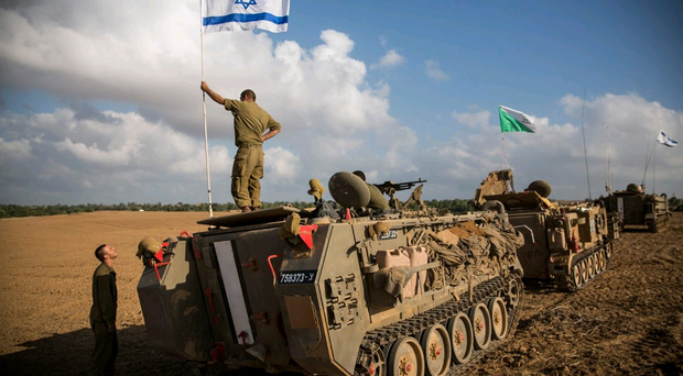 An Israeli soldier stands on top of an armoured personnel carrier (Photo by Andrew Burton/Getty Images)
