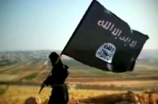 A man holding the flag of Islamic State in Iraq and al-Sham (Isis) walks across a hill in a propaganda video for the organisation