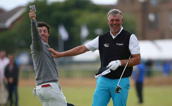 HOYLAKE, ENGLAND - JULY 16: Rory McIlroy (L) of Northern Ireland takes a bank note in celebration of winning a bet against Darren Clarke (R) after their practice round prior to the start of The 143rd Open Championship at Royal Liverpool on July 16, 2014 in Hoylake, England. (Photo by Matthew Lewis/Getty Images)