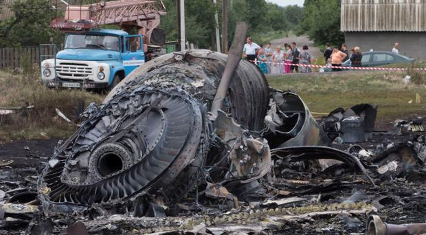 Local citizens, background, look at the site of a crashed Malaysia Airlines passenger plane near the village of Rozsypne, Ukraine