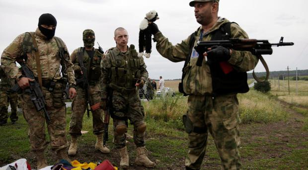 A pro-Russian fighter holds up a toy found among the debris at the crash site of a Malaysia Airlines jet near the village of Hrabove, Friday, July 18, 2014. Emergency workers, police officers and even off-duty coal miners spread out Friday across the sunflower fields and villages of eastern Ukraine, searching the wreckage of a Malaysia Airlines jet shot down as it flew high above the country's battlefield. The attack Thursday afternoon killed 298 people from nearly a dozen nations. (AP Photo/Dmitry Lovetsky)