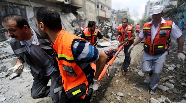 Palestinian medics carry a man injured in Gaza City's Shijaiyah neighborhood that came under fire as Israel widened its ground offensive against Hamas in the northern Gaza Strip on Sunday, July 20, 2014. Tens of people were killed in Shijaiyah and many more bodies were believed buried under the rubble of homes, health officials said. They are the latest casualties in a nearly two-week conflict that has killed some 380 Palestinians and seven Israelis. (AP Photo/Hatem Moussa)