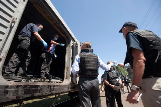 Deputy head of the OSCE mission to Ukraine Alexander Hug, center back to the camera, speaks to a member of Netherlands' National Forensic Investigations Team on the platform as a refrigerated train loaded with bodies of the passengers departs the station in Torez, eastern Ukraine. (AP Photo/Evgeniy Maloletka)