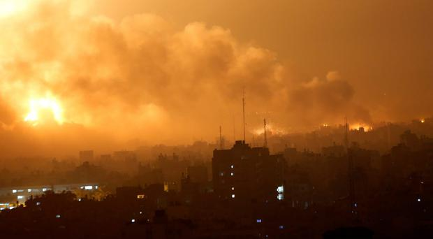 Smoke rises as flames spread across buildings after Israeli strikes in the Shijaiyah neighborhood in Gaza City, Tuesday, July 22, 2014. (AP Photo/Khalil Hamra)