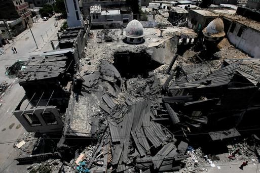 Palestinians inspect Al Farouk mosque destroyed by an overnight Israeli strike, in Rafah, in the southern Gaza Strip, Tuesday, July 22, 2014. (AP Photo/Eyad Baba)