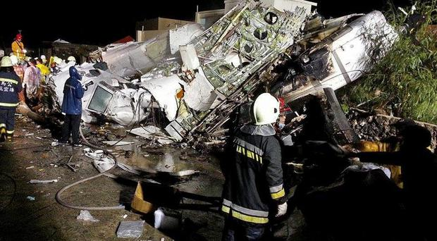Rescue workers survey the wreckage of TransAsia Airways flight GE222 which crashed while attempting to land in stormy weather on the Taiwanese island of Penghu, late Wednesday, July 23, 2014. A plane landing in stormy weather crashed outside an airport on a small Taiwanese island late Wednesday, and a transport minister said dozens of people were trapped and feared dead. (AP Photo/Wong Yao-wen)