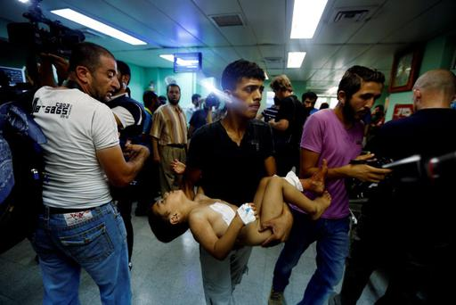 A Palestinian man carries a child, wounded in an Israeli strike on a compound housing a U.N. school in Beit Hanoun, in the northern Gaza Strip, cries at the emergency room of the Kamal Adwan hospital in Beit Lahiya, Thursday, July 24, 2014. (AP Photo/Lefteris Pitarakis)