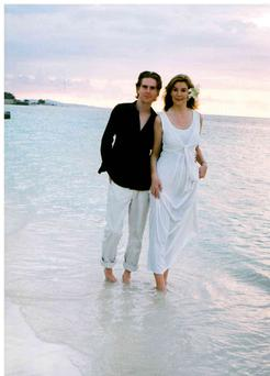 Una Brankin posing for pictures on the beach in her simple white sun dress with husband Declan