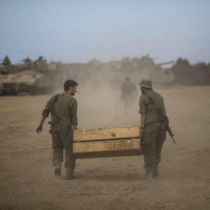 Israeli soldiers seen carrying tank ammo near the Israeli-Gaza border on July 25, 2014 near Israel's border with the Gaza Strip. (Photo by Ilia Yefimovich/Getty Images)