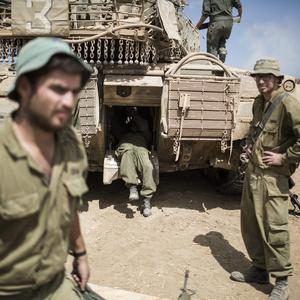 Israeli soldiers seen working on a tank near the Israeli-Gaza border on July 25, 2014 near Israel's border with the Gaza Strip. (Photo by Ilia Yefimovich/Getty Images)