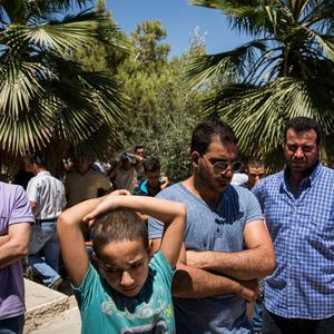 Men attend the burial of Mohammed al-Araj during his funeral on July 25, 2014 near Ramallah, West Bank. (Photo by Andrew Burton/Getty Images)