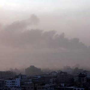 Amidst the morning fog, smoke from an Israeli strike rises in the air over Gaza City, Saturday, July 26, 2014. (AP Photo/Lefteris Pitarakis)