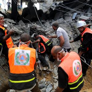 Palestinian medics dig out a body found under the rubbles of a home destroyed by an Israeli strike in Khan Younis in the southern Gaza Strip, Friday, July 25, 2014. (AP Photo/Hatem Moussa)