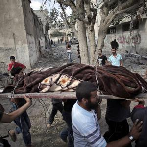 Palestinians carry a body of a man found under the rubble of a destroyed house during a 12-hour cease-fire in Gaza City's Shijaiyah neighborhood, Saturday, July 26, 2014. (AP Photo/Khalil Hamra)