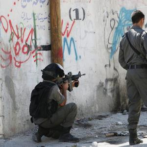 An Israeli soldier aims at Palestinian protesters during clashes in Hawara village near the West Bank city of Nablus on Friday, July 25, 2014. (AP Photo/Nasser Ishtayeh)