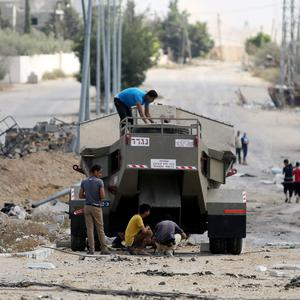 Palestinian men climb on Israel's military vehicle that was left behind by the forces in Gaza City's Shijaiyah neighborhood, Saturday, July 26, 2014. (AP Photo/Hatem Moussa)