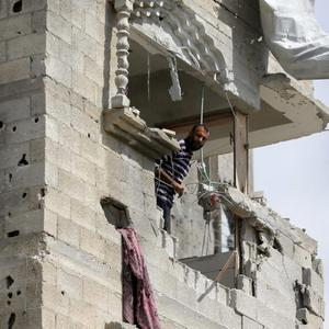 A Palestinian look outside from his destroyed house as he visits the area during a 12-hour cease-fire in Gaza City's Shijaiyah neighborhood, Saturday, July 26, 2014. (AP Photo/Hatem Moussa)