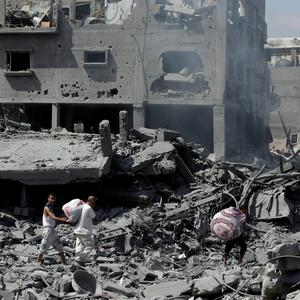 Palestinians carry their belongings through rubble of houses destroyed by Israeli strikes, as they visit the area during a 12-hour cease-fire in Beit Hanoun, northern Gaza Strip, Saturday, July 26, 2014. (AP Photo/Lefteris Pitarakis)