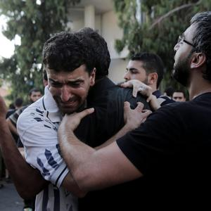 Palestinian relatives comfort each other in front of the morgue of Shifa hospital following an explosion that killed 10 people, nine of them children at a park at Shati refugee camp, in Gaza city, in the northern Gaza Strip, Monday, July 28, 2014 (AP Photo/Adel Hana)