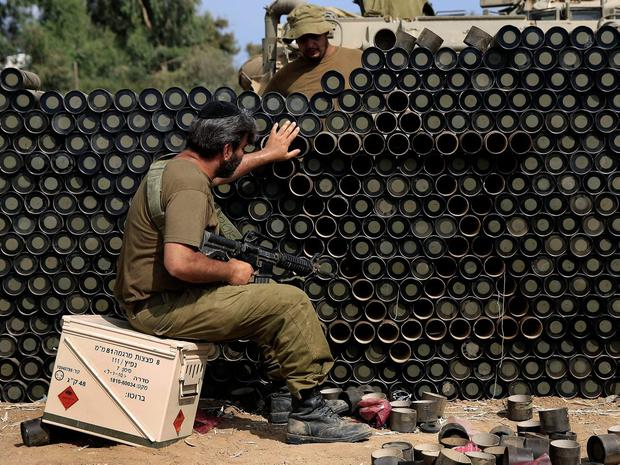 An Israeli reserve soldier makes a wall with the Star of David from cardboard mortar shell boxes near the Israel Gaza border, Monday, July 28, 2014. (AP Photo/Tsafrir Abayov)