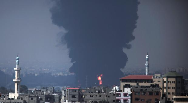 Seen from Gaza City, smoke and flames rise from Gaza's electricity distribution company plant after it was hit by Israeli strikes in the Nusseirat refugee camp, central Gaza Strip,Tuesday, July 29, 2014 (AP Photo/Lefteris Pitarakis)