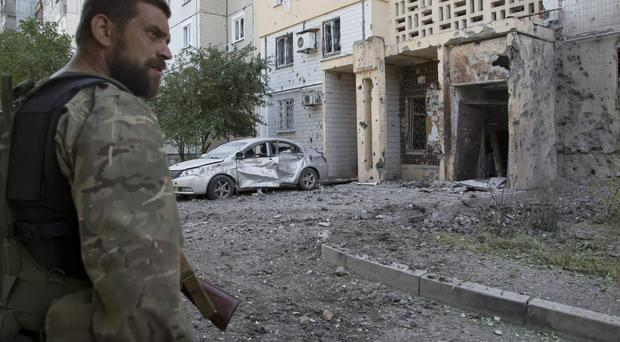 A pro-Russian fighter walks near to a damaged residential building, as the body of a community service worker who was killed during the shelling lays outside the doorway at right, in Donetsk, eastern Ukraine Tuesday, July 29, 2014. Local residents said it was a shelling from direction of Ukrainian army's positions.(AP Photo/Dmitry Lovetsky)