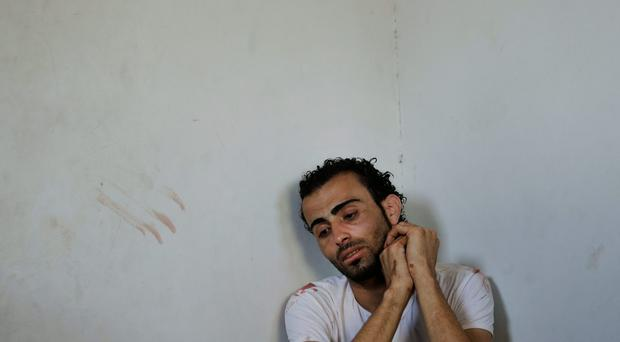 A Palestinian weeps as he attends the bodies of Shaher al-Najar and his brother Bassem, killed in an Israeli strike, Wednesday, July 30, 2014. (AP Photo/Lefteris Pitarakis)