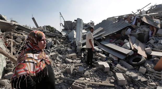 Palestinian Abir Wahdan, 39, left, and her husband Muhammed, inspect the rubble of what used to be their family house in the heavily bombed town of Beit Hanoun, Gaza Strip, close to the Israeli border, Friday, Aug. 1, 2014. (AP Photo/Lefteris Pitarakis)