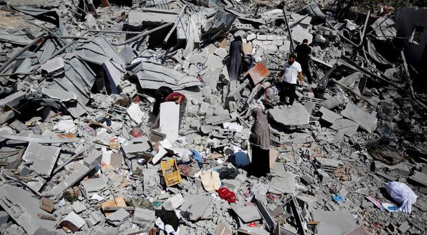 Palestinians search the rubble their home in Beit Hanoun, Gaza Strip, Friday, Aug. 1, 2014. (AP Photo/Hatem Moussa)