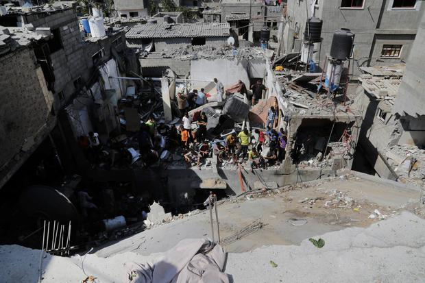 Palestinians search for bodies at the rubble of the destroyed house for the Bayoumi family in the Nusseirat refugee camp in the central Gaza Strip on Friday, Aug. 1, 2014. (AP Photo/Adel Hana)