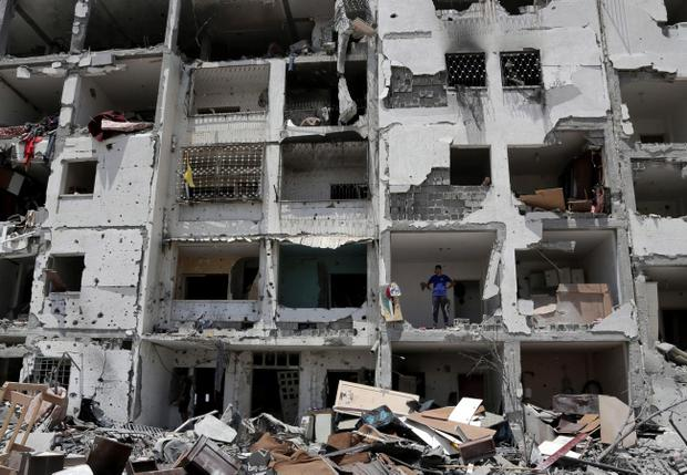 A Palestinian stands amid the rubble of his bedroom in a building destroyed by Israeli strikes in Beit Lahiya, in the northern Gaza Strip, Monday, Aug. 4, 2014. (AP Photo/Adel Hana)