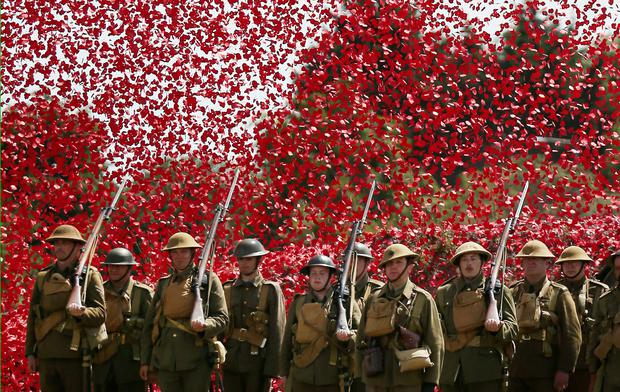 BOVINGTON, UNITED KINGDOM - AUGUST 04: Members of the Great War Society living history group dressed as 4th Battalion the Middlesex Regiment stand under a shower of a million poppy flowers representing the dead during a World War One centenary ceremony at the Tank Museum, Bovington on August 4, 2014 in England. (Photo by Peter Macdiarmid/Getty Images)