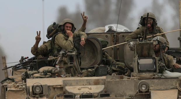 Reserve soldiers are seen on the top of an armored personnel carrier: Israeli military has announced the withdrawal of all its ground forces to defensive positions
