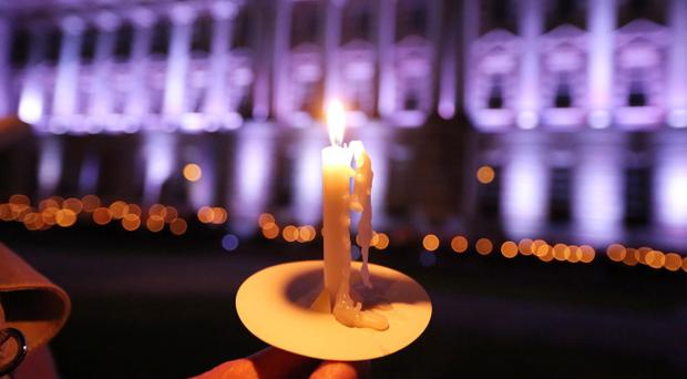 A candle is held in front of Belfast City Hall as the building was plunged into darkness to mark the centenary of the beginning of the First World War