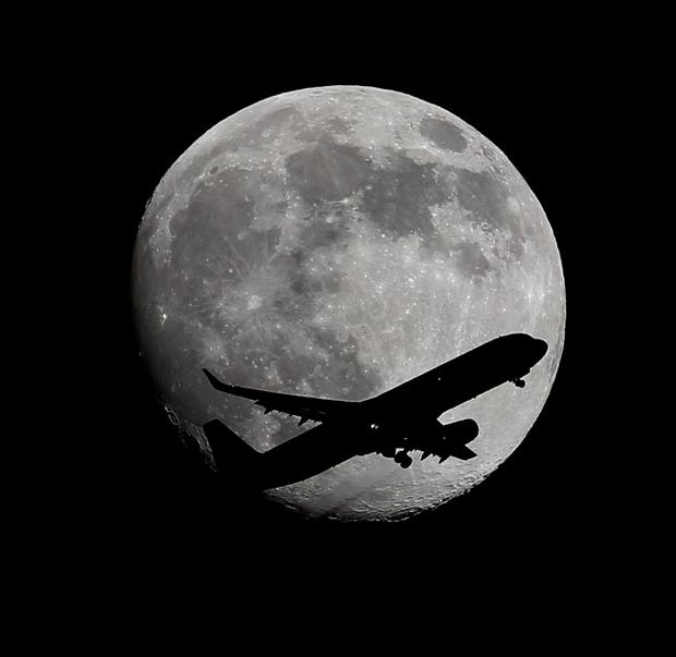 An LAX bound passenger airplane drops the wheels as it crosses the moon two days before the Full Moon and Super Moon passing over Whittier, CA., on its final approach to the Los Angeles Airport, on Friday, Aug. 8, 2014. (AP Photo/Nick Ut )