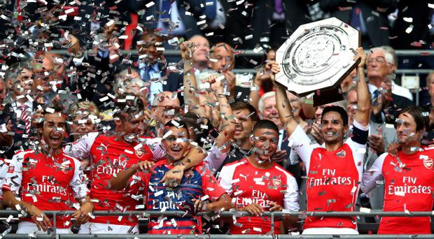 Captain Mikel Arteta of Arsenal holds up the trophy after winning the FA Community Shield match against Manchester (Photo by Clive Mason/Getty Images)